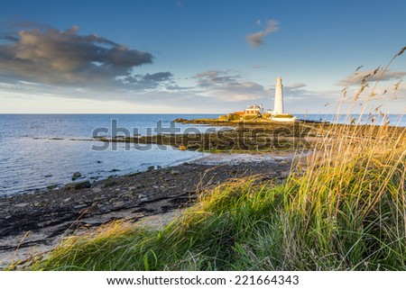 St Mary's Island basked in the evening light against beautiful sky - stock photo