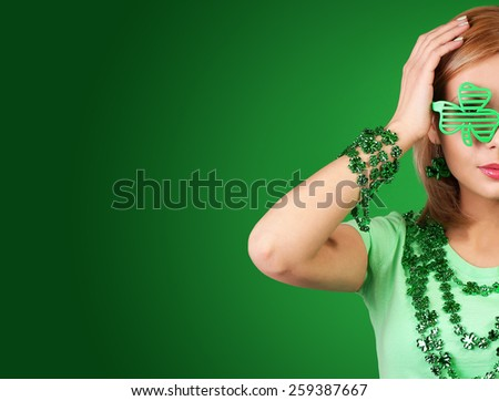 St Patrick's day Girl. Blonde Young woman wearing shamrock shaped glasses over green background - stock photo