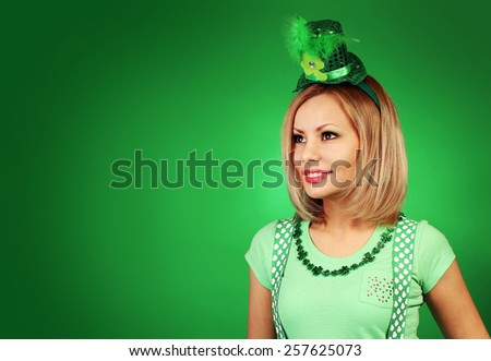 St Patrick's day Girl. Happy blonde young woman with hat over green background - stock photo
