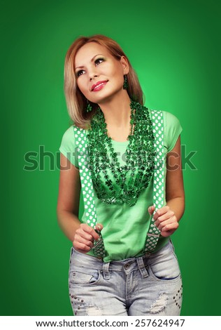 St Patrick's day Girl. Happy young woman with shiny necklaces and suspenders over green background - stock photo