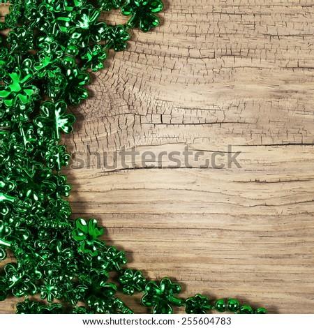 St. Patrick's Day. Shamrock Shaped Shiny Leaves over Wooden Background - stock photo