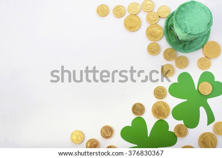 St Patricks Day Flat Lay including leprechaun hat, chocolate gold covered coins and shamrocks on white wood background, with copy space.  - stock photo