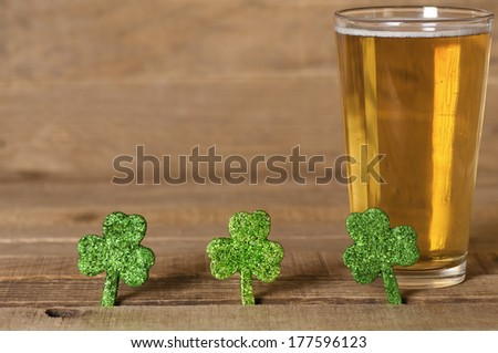 St. Patricks Day green Shamrocks with a full cold frosty glass of beer on rustic wood board background with room or space for text, copy, words. - stock photo