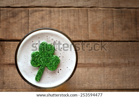 St. Patricks Day Shamrock Floating in Frothy Beer Mug on rustic wood board background with room or space for copy, text, your words.  Closeup Above View Horizontal with warm tone  - stock photo