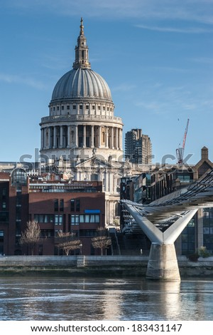 St Paul's Cathedral in London seen from the Millennium Bridge at sunrise on a beautiful sunny day in 2014. Available space for text on both upper sides of the image. - stock photo