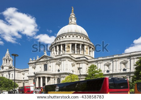 St Paul's Cathedral in London with red buses, with blue sky and white cloud - stock photo