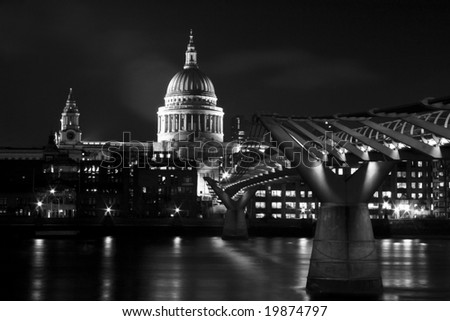 St. Paul's Cathedral on the Thames River with the Millennium Bridge in London, England. - stock photo
