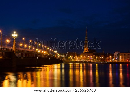 St. Peter's Church and bridge across Daugava river in Riga at night - stock photo