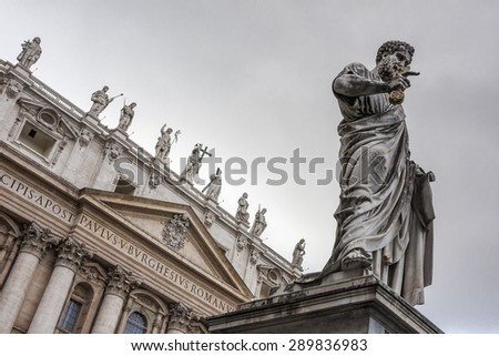 St. Peter under the dark clouds, Vatican City. Low angle view of the statue of St. Peter in St. Peter's Square, Vatican City, with the front of the famous Basilica in the background. - stock photo
