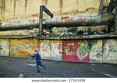 ST PETERSBURG, RUSSIA-APRIL 12, 2008: Boy playing soccer in poor area in city outskirts in Saint Petersburg, Russia - stock photo