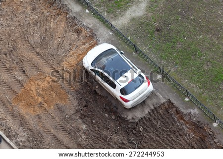 ST. PETERSBURG, RUSSIA - CIRCA APR, 2015: Wrong parking vehicle is on middle of lawn while construction machinery works for extension of parking area of building. Creation of living environment - stock photo