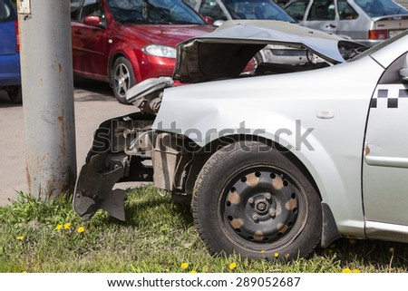 ST. PETERSBURG, RUSSIA - CIRCA MAY, 2015: Broken taxi car is on pavement after frontal collision with pole. Accident with passing crossroads at a red light. No one injured. - stock photo