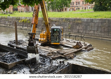 ST. PETERSBURG, RUSSIA - JULY 26, 2015: Working on the dredger clears the bottom of the canal from the scrap metal and sediment - stock photo