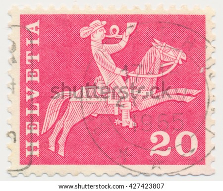 ST. PETERSBURG, RUSSIA - MAY 11, 2016: A postmark printed in SWITZERLAND, shows Postman on horseback blows a horn, circa 1965 - stock photo
