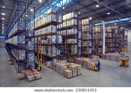 St. Petersburg, Russia - November 21, 2008: Forklift palletiser carrying palletising on the territory of  warehouse. The interior of a large goods warehouse with shelves of pallet rack system storage. - stock photo