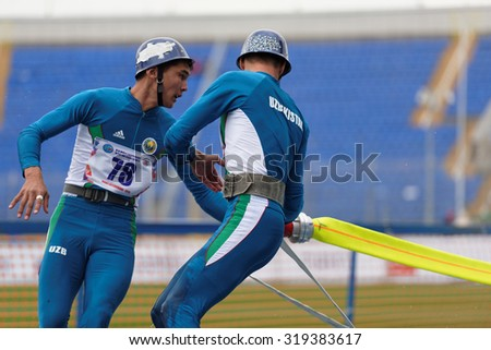 ST. PETERSBURG, RUSSIA - SEPTEMBER 9, 2015: Team Uzbekistan compete in combat deployment during XI World Championship in Fire and Rescue Sport. First World Championship was held in 2002 - stock photo
