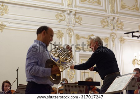 ST. PETERSBURG, RUSSIA - SEPTEMBER 7, 2015: Virtuoso horn players Hermann Baumann (right) and Javier Bonet on the rehearsal with symphonic orchestra Nevsky during International festival of French horn - stock photo