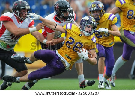 ST. POELTEN, AUSTRIA - JULY 26, 2014: RB Alexander Hertel (#28 Vikings) runs with the ball during Silver Bowl XVII. - stock photo