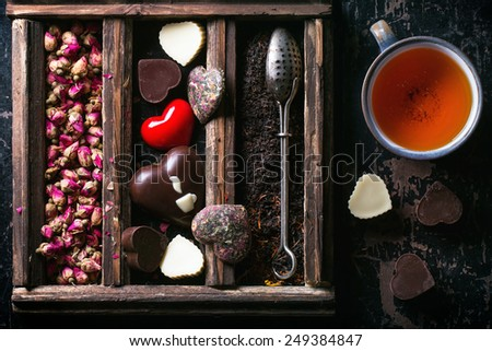 st Valentine greeting card with set of dry tea, heart from tea and chocolate and cup of tea. Top view. - stock photo