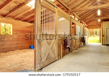 Stable barn with beam ceiling and open door to a clean stall. - stock photo
