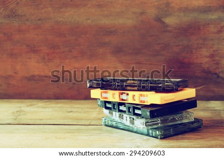 stack Cassette tapes over wooden table. retro filter - stock photo
