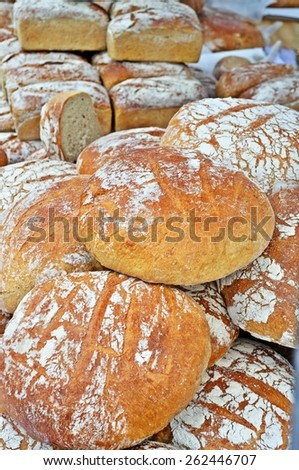 Stack loaves of artisan bread on the stand with the regional food at farmer's market  - stock photo