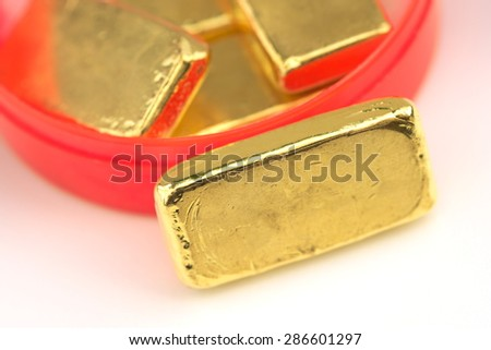 Stack of actual smallest gold bar commonly sold in Thailand with red container round box over white table. Each bar is 96.5% purity gold which is roughly equal to 99.5% purity 2.527 troy ounce. - stock photo