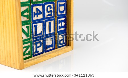 Stack of alphabet block letters and numbers in a cube wooden box. Concept of basic structure of spelling education. Isolated on white background. Slightly de-focused and close-up shot. Copy space. - stock photo