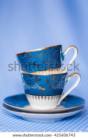 Stack of antique tea cups on blue background - stock photo