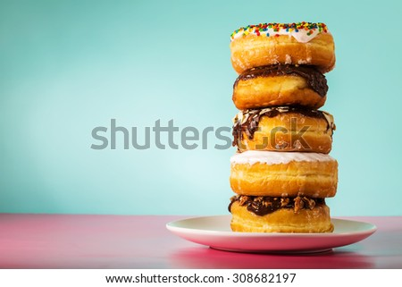 Stack of assorted donuts on a white plate on pastel blue and pink background - stock photo