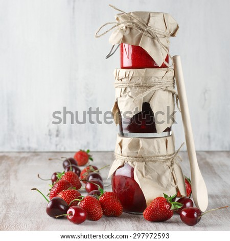 Stack of assorted jams in glass jars with wood spoon and fresh berries on rustic wooden background. - stock photo