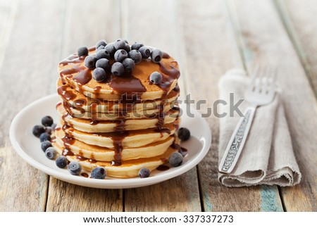 Stack of baked pancakes or fritters with chocolate sauce and frozen blueberries in a white plate on a wooden rustic table, delicious dessert for breakfast - stock photo