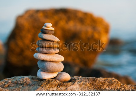 Stack of balanced pebbles, stones against colorful rock - stock photo