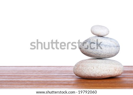 Stack of balanced stones with shadow on wooden background - stock photo