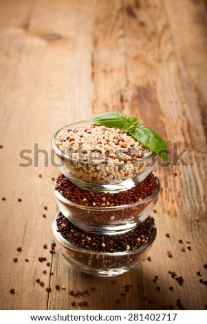 Stack of bawls with red, black and mixed raw quinoa, South American grain on old rustic wooden background.  Background with copy space. Toned. - stock photo
