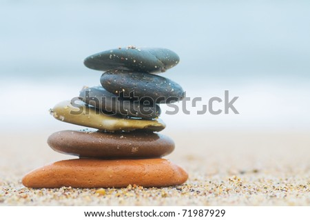 Stack of beach stones on sand. Ocean in the background - stock photo