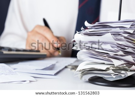 Stack of bills in paper nail with businessman calculating - stock photo