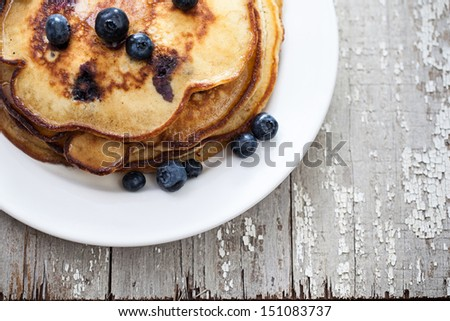 Stack of blueberry pancakes on a plate with blueberries on a rustic wooden table - stock photo