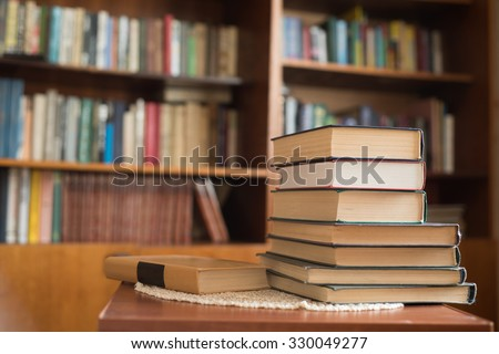 Stack of books and books on bookshelves - stock photo