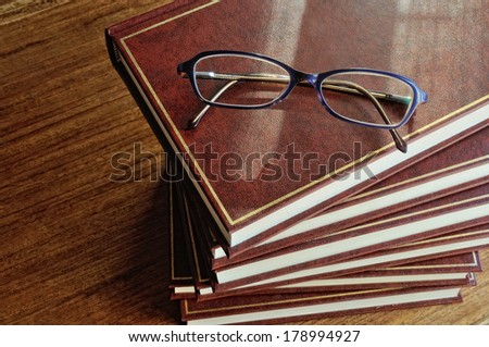 stack of books and glasses on tablel top view - stock photo