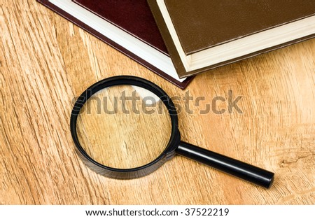 stack of books and magnifying glass - stock photo