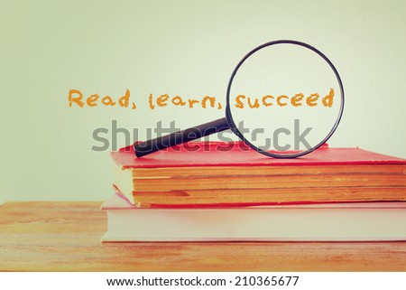 stack of books and magnifying glass with the phrase learn read succeed. education concept - stock photo