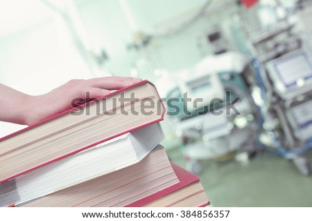 Stack of books in hospital ward, concept of professional development. - stock photo