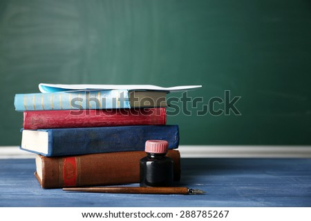 Stack of books on desk, on blackboard background - stock photo