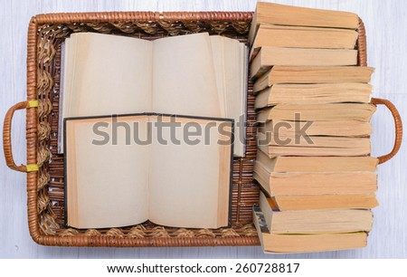 stack of books on the wicker wooden tray - stock photo