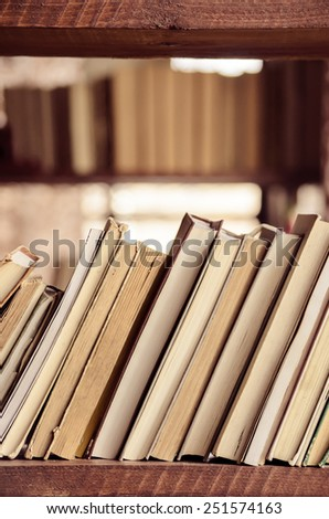 Stack of books on the wooden shelf. - stock photo