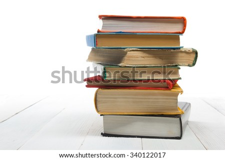 Stack of books on wooden shelf isolated on white background. Back to school. Copy space for text - stock photo