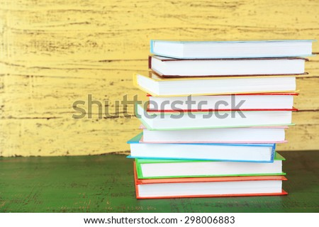 Stack of books on yellow wooden background - stock photo