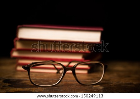Stack of books with a pair of glasses - stock photo