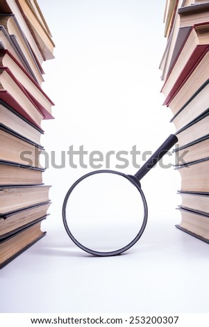 Stack of books with magnifying glass. - stock photo